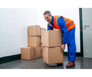 man strains back lifting boxes